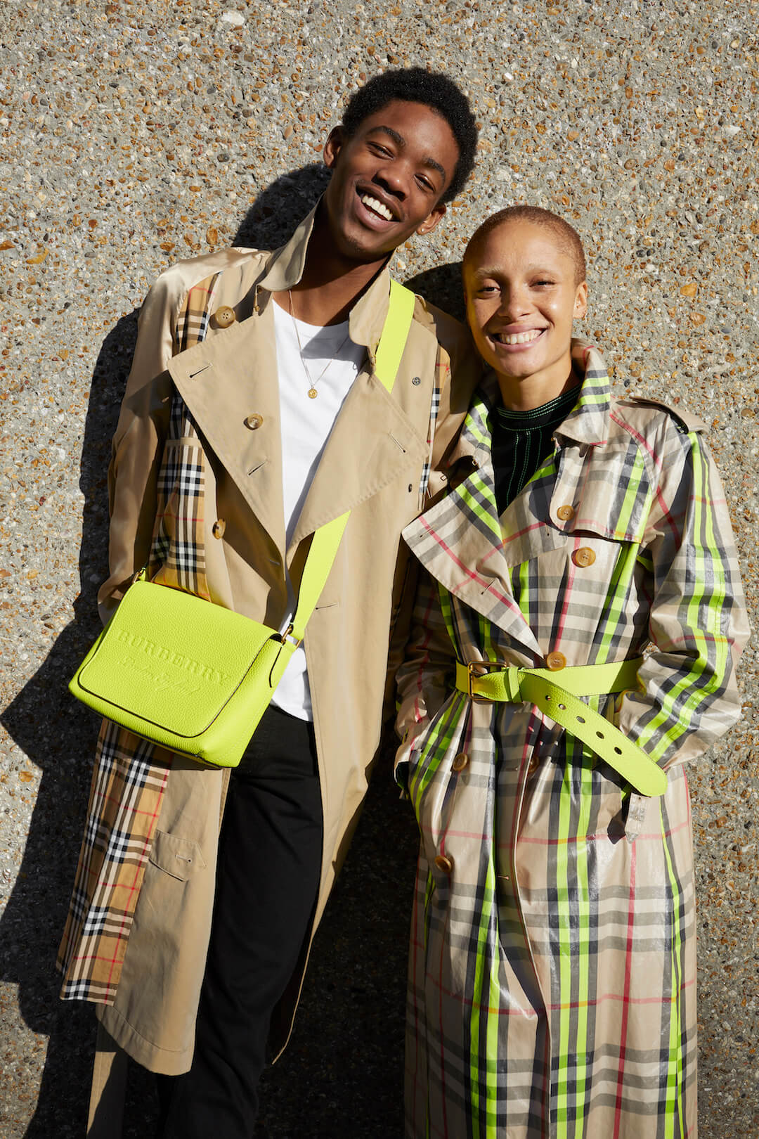 Montell Martin wearing a trench coat and neon soft leather crossbody bag and Adwoa Aboah wearing a laminated fluoro-trimmed check trench coat for Burberry captured by Juergen Teller